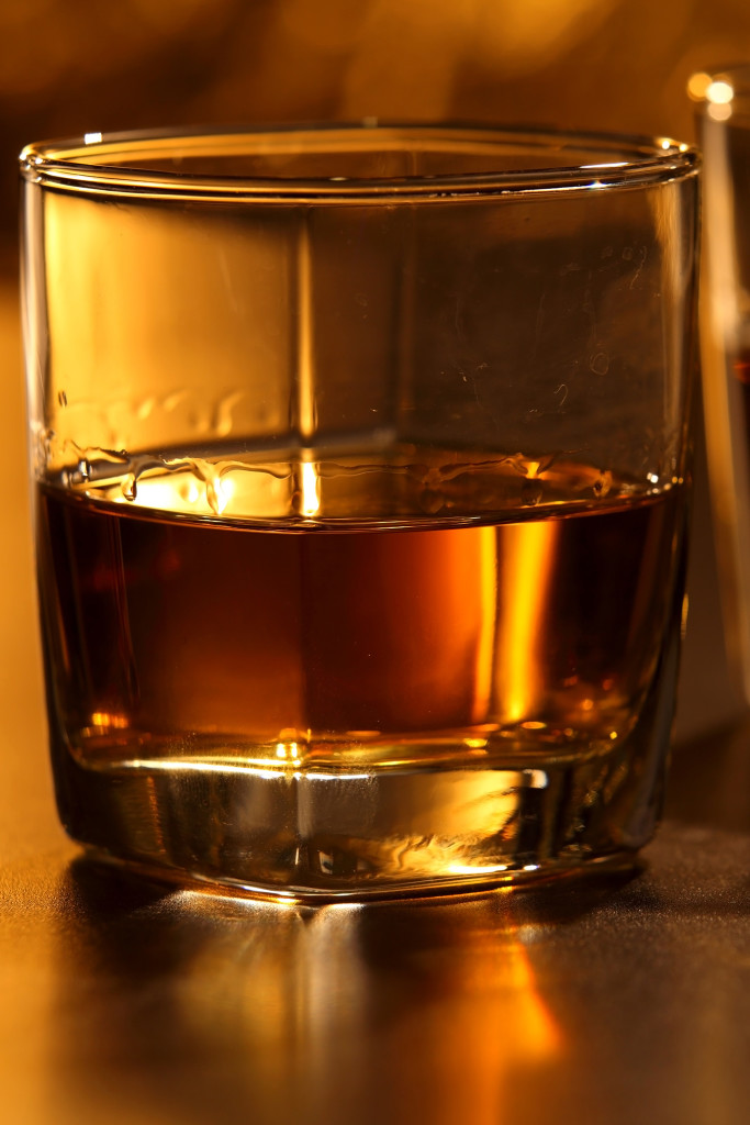 Glass of whiskey and ice on brown bar counter